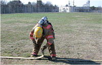 Fire fighter examines the hose connections.