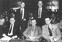 Photo of the Raymond Hamilton trial, with the lawyers around the defendant.