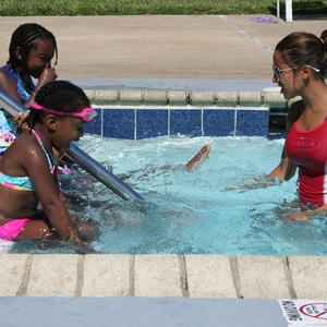 Life Guard Giving Girls a Swimming Lesson