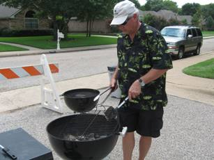Man Stirring Coals in a Grill