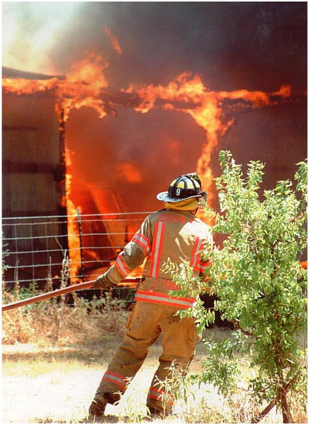 Fire fighter pulls hose to get a better angle against a fire.