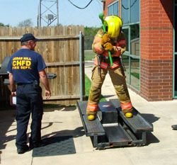 Fire fighter using sledge hammer to move an I-beam, while standing on the sled.