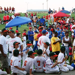 Teams in little league baseball wait for their turn to play.